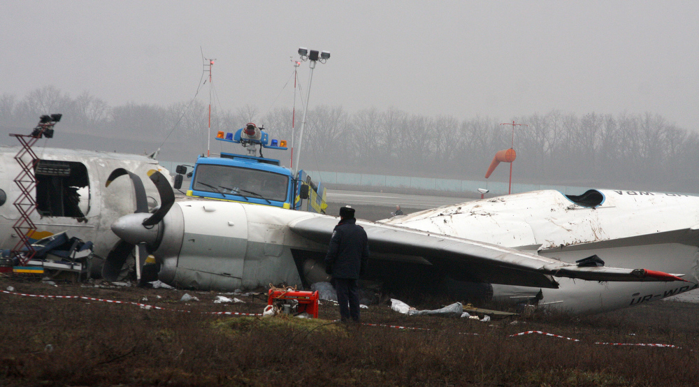 . An official stands near a Ukrainian AN-24 plane after it crashed outside an airport  in the eastern Ukrainian city of Donetsk, Thursday, Feb. 14, 2013. The passenger plane carrying soccer fans headed for a match between Shakhtar and Borussia Dortmund, skidded past the landing strip and overturned on Wednesday, killing five people. The plane was carrying 44 passengers and crew from the Black Sea port of Odessa. (AP Photo/Irina Gorbaseva)