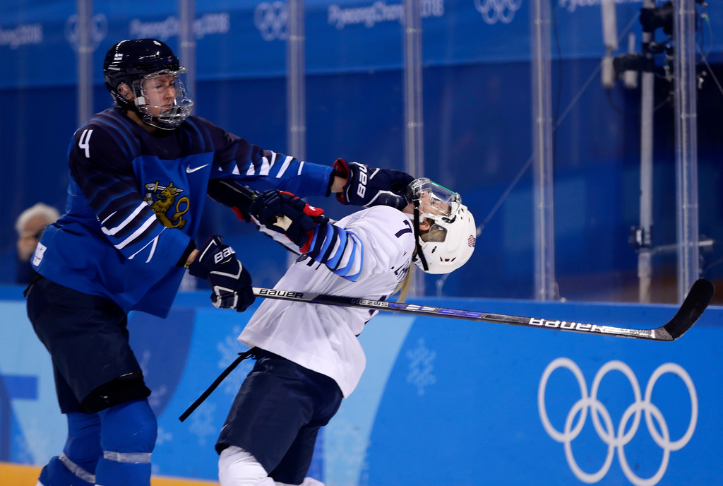 . Monique Lamoureux-Morando (7), of the United States, takes a punch from Rosa Lindstedt (4), of Finland, during the second period of the preliminary round of the women\'s hockey game at the 2018 Winter Olympics in Gangneung, South Korea, Sunday, Feb. 11, 2018. (AP Photo/Frank Franklin II)
