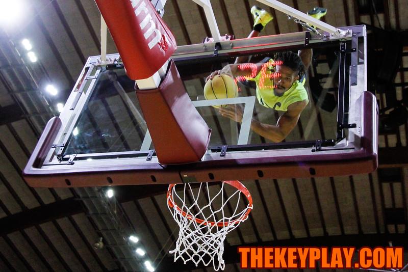 A member of the Acrodunk dunk team flips off the backboard during the halftime show. (Mark Umansky/TheKeyPlay.com)