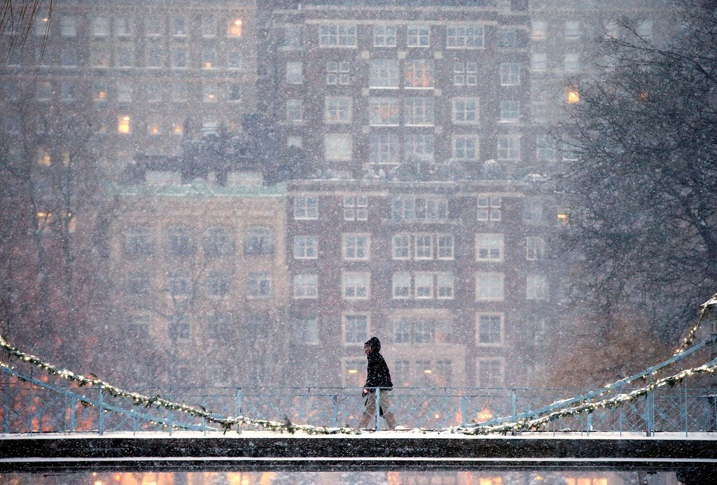 . A person crosses the pedestrian bridge in the Public Garden during a winter storm in Boston, Saturday, Jan. 7, 2017. (AP Photo/Michael Dwyer)