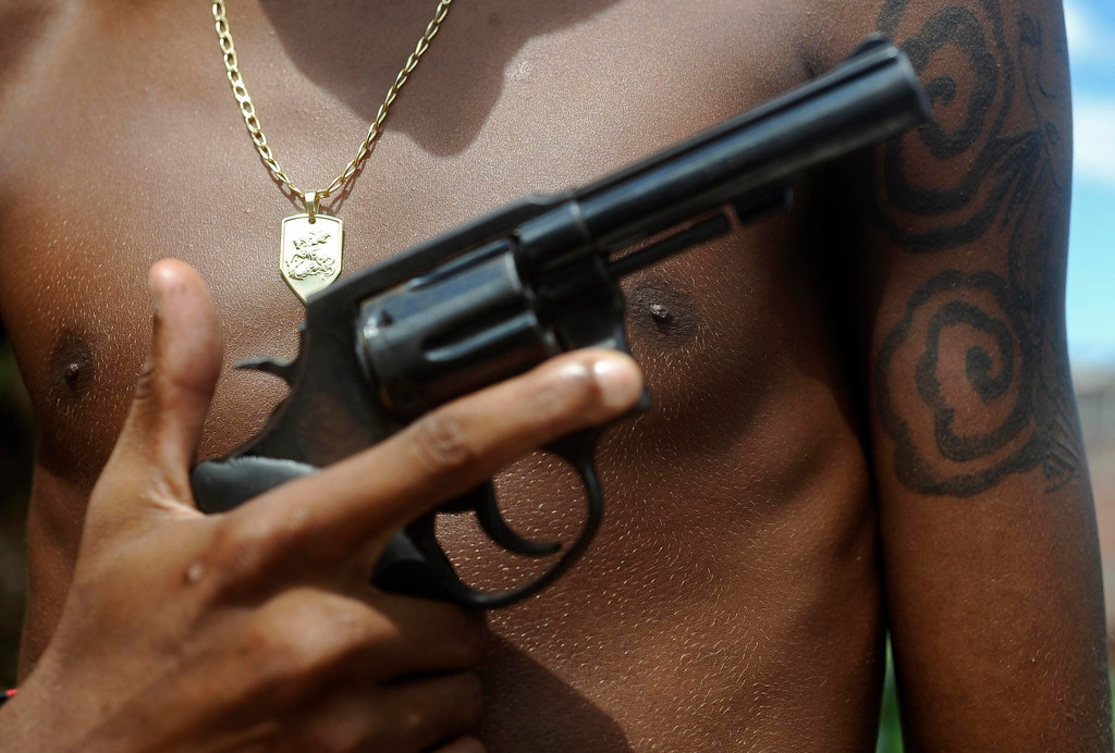 . A Brazilian drug gang member nicknamed Giant, 17, poses with a gun and his medallion of St. George, in a slum in Salvador, Bahia State, April 11, 2013. One of Brazil\'s main tourist destinations and a 2014 World Cup host city, Salvador suffers from an unprecedented wave of violence with an increase of over 250% in the murder rate, according to the Brazilian Center for Latin American Studies (CEBELA). Picture taken April 11, 2013.  REUTERS/Lunae Parracho