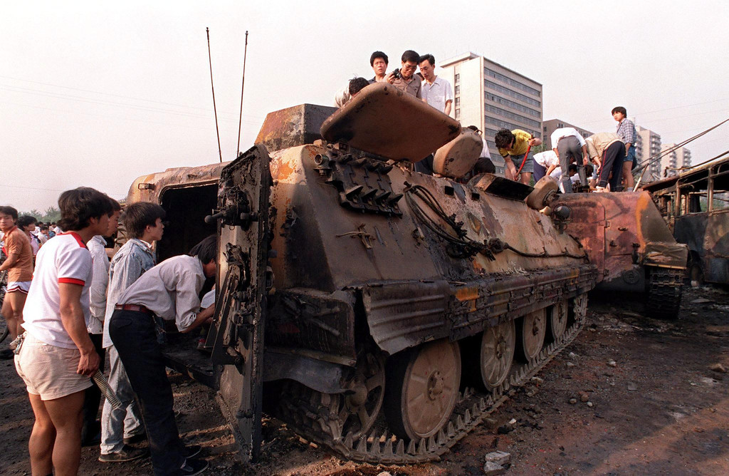 . Beijing residents inspect the interior of one of over 20 armored personnel carriers burned by demonstrators to prevent the troops from moving into Tiananmen Square 04 June 1989. (MANUEL CENETA/AFP/Getty Images)