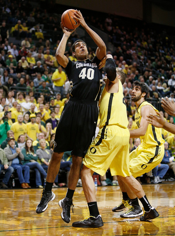 . Colorado\'s Josh Scott puts up a shot in front of Oregon defenders Waverly Austin and Arsalan Kazemi, right,  during the first half of Colorado\'s game against Oregon in an NCAA college basketball game at Matthew Knight Arena in Eugene, Ore. Thursday, Feb. 7, 2013. (AP Photo/Brian Davies)
