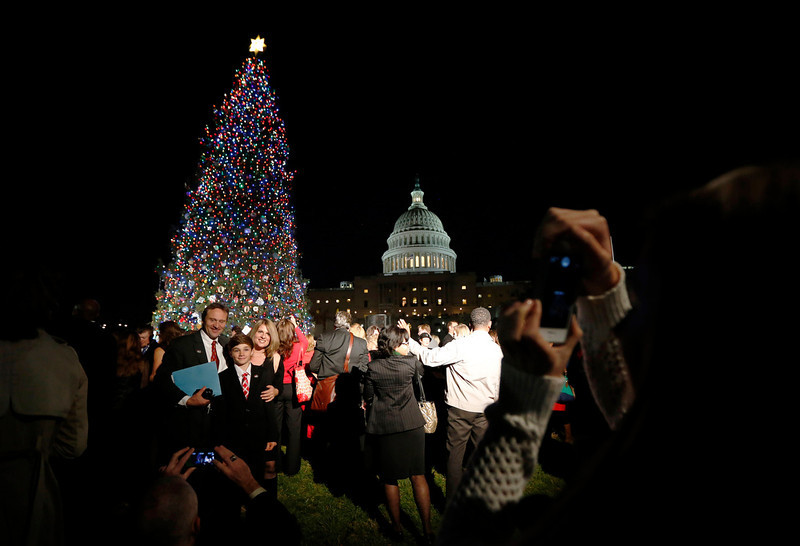 . A family have their picture taken during the official lighting ceremony of the U.S. Capitol Christmas Tree in Washington December 4, 2012.     REUTERS/Jason Reed