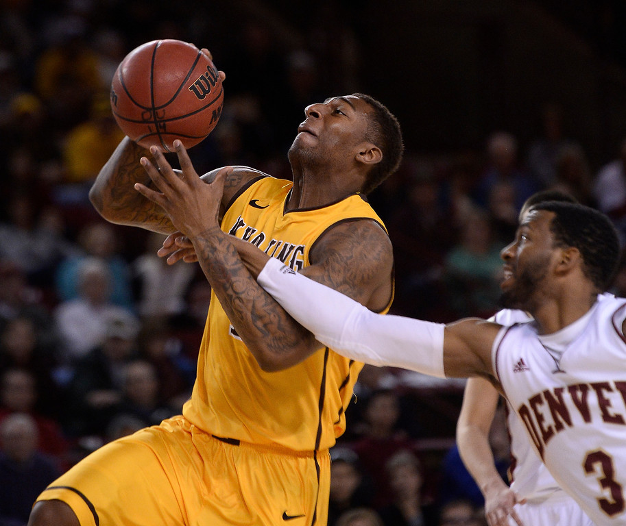 . Wyoming Cowboys guard Charles Hankerson Jr. (1) gets hit on the arm by Denver Pioneers guard Jalen Love (3) as he loses control of the ball during the first half December 15, 2013 Magness Arena. (Photo by John Leyba/The Denver Post)