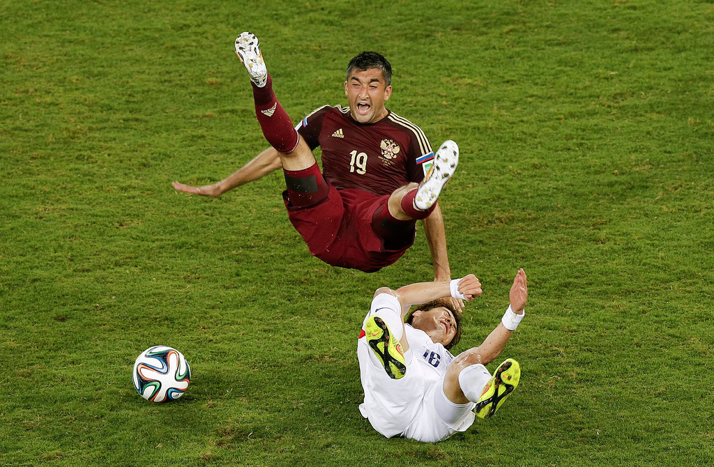 . South Korea\'s Ki Sung-yueng, bottom, fouls Russia\'s Alexander Samedov during the group H World Cup soccer match between Russia and South Korea at the Arena Pantanal in Cuiaba, Brazil, Tuesday, June 17, 2014. (AP Photo/Thanassis Stavrakis)