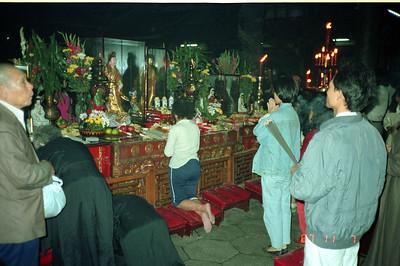 Praying to ancestors at temple alter.  Taipei.