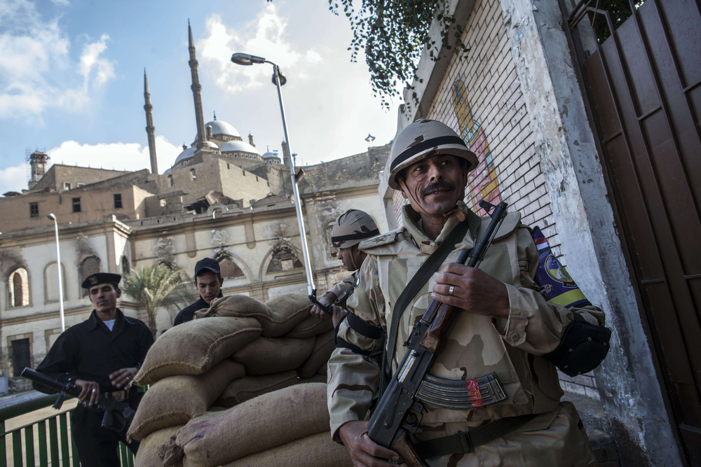 . Members of the Egyptian security forces stand guard outside a polling station near The Saladin Citadel (background) on Mokattam hill near the center of Cairo during the second day of voting on a new constitution on January 15, 2014. Egyptians resumed voting in the constitutional referendum, with turnout expected to hold the key to a likely presidential bid by army chief Abdel Fattah al-Sisi after clashes killed nine the previous day. (MAHMOUD KHALED/AFP/Getty Images)
