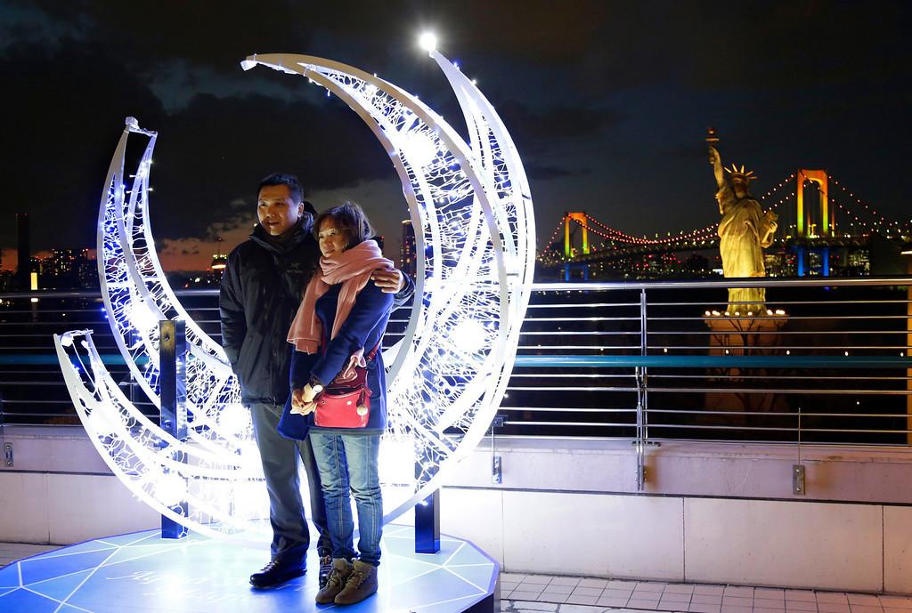 . A couple poses in front of the Christmas illuminations for souvenir photos at Tokyo\'s Daiba bay area, Tuesday, Dec. 24, 2013. (AP Photo/Shizuo Kambayashi)