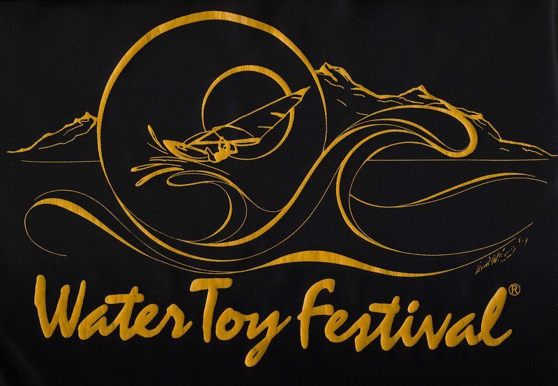 "The original ""Water Toy Festival"" logo - design by Dave Evers and printed by Bruce Lavoni on black jackets. Water Toy Festival was a Foonman Production brain child of Larry Schmidt that attracted many of Copper Mt emps to a good time at the lake. The sail board craze was in full force in these days."