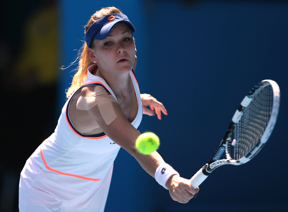 . Agnieszka Radwanska of Poland makes a backhand return to Dominika Cibulkova of Slovakia during their semifinal at the Australian Open tennis championship in Melbourne, Australia, Thursday, Jan. 23, 2014.(AP Photo/Aaron Favila)