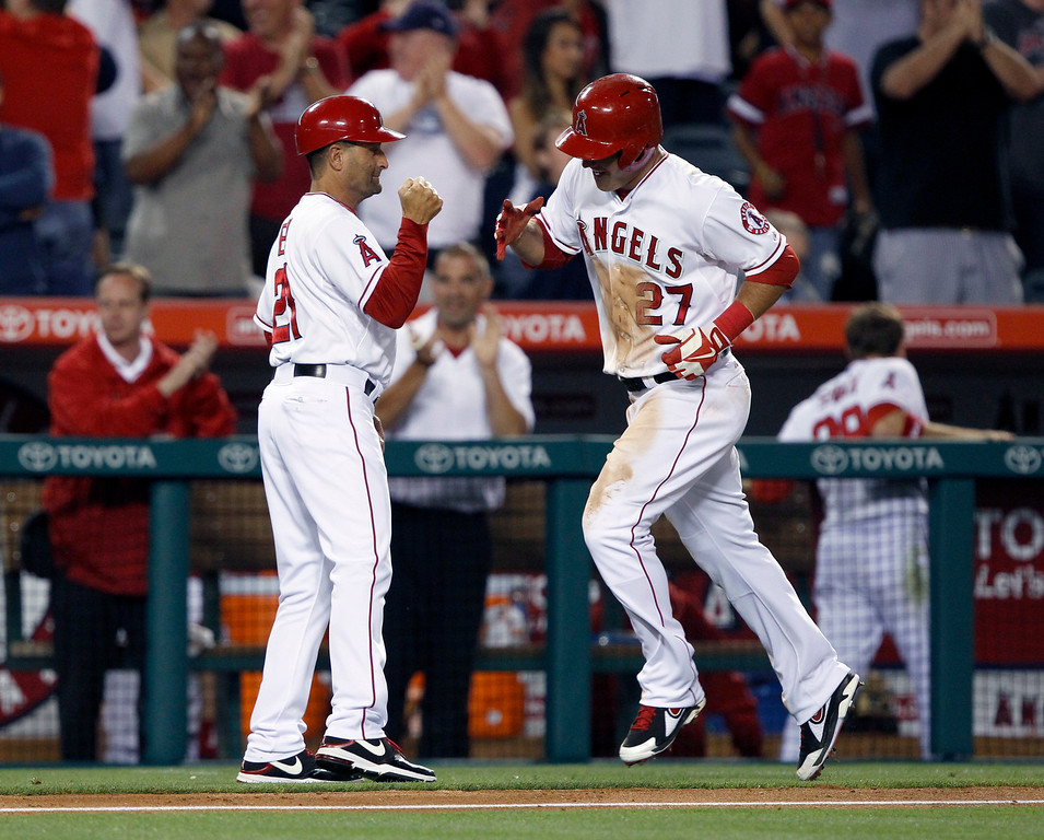 . Los Angeles Angels\' third base coach Dino Ebel , left, congratulates Mike Trout (27) for hitting a solo home run in the eighth inning, to hit for the cycle against the Seattle Mariners during a baseball game Tuesday, May 21, 2013 in Anaheim.  The Angels won the game 12-0.   (AP Photo/Alex Gallardo)