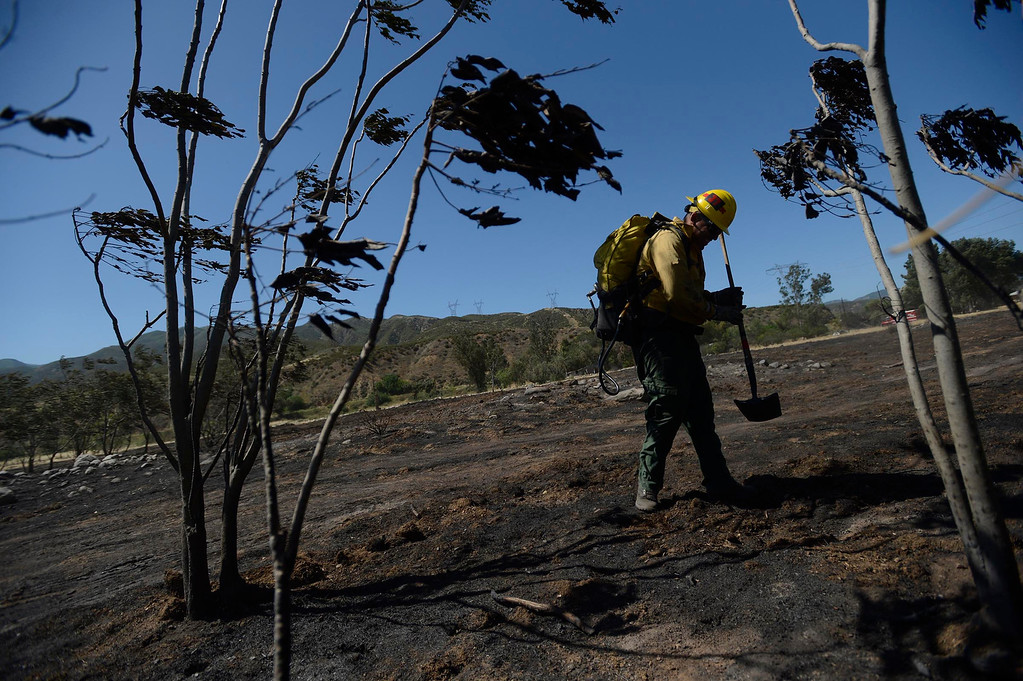 . U.S. Forest Service firefighter Mike Duran stamps out some hot spots along the I-15 freeway in North Fontana May 14, 2013.  GABRIEL LUIS ACOSTA/STAFF PHOTOGRAPHER.