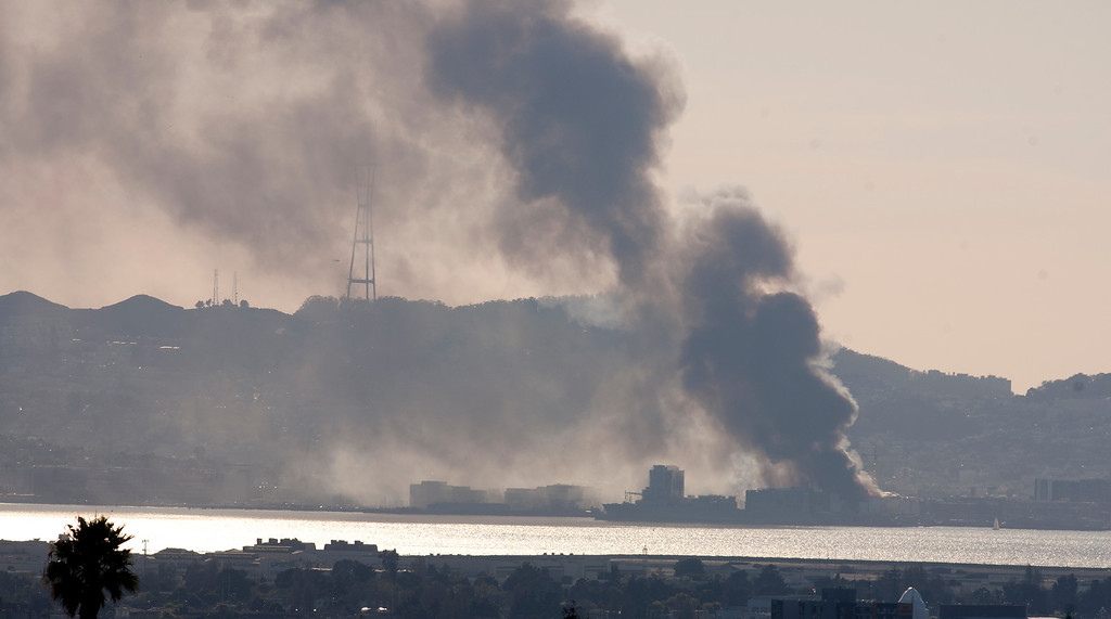 . A plume of smoke rises from a five-alarm fire at a residential construction site in the South of Market neighborhood of San Francisco, as seen from the Oakland, Calif., hills on Tuesday, March 11, 2014. More than 100 firefighters responded to the blaze, which threatened to destroy the building under construction, as well as occupied structures in the neighborhood. (D. Ross Cameron/Bay Area News Group)