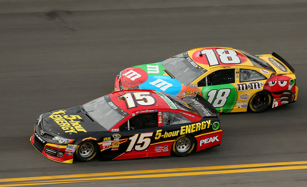 . Clint Bowyer, driver of the #15 5-hour ENERGY Toyota, and Kyle Busch, driver of the #18 M&M\'s Toyota, race during the NASCAR Sprint Cup Series Budweiser Duel 2 at Daytona International Speedway on February 21, 2013 in Daytona Beach, Florida.  (Photo by Mike Ehrmann/Getty Images)