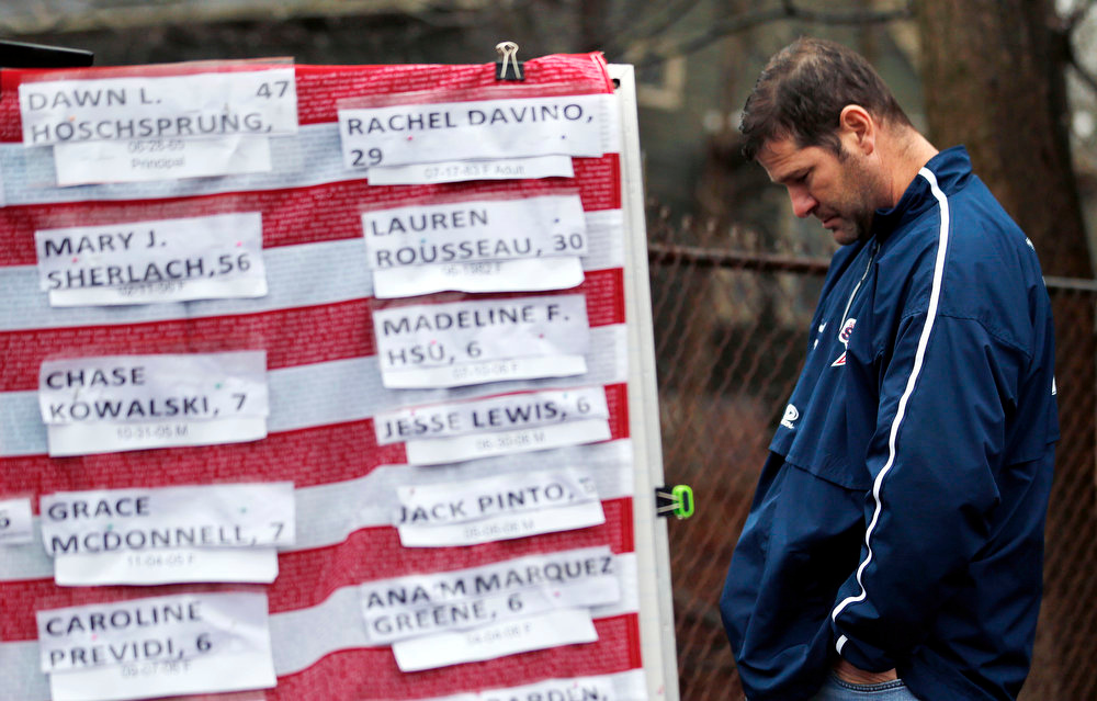 Description of . A man pays respects near a U.S. flag donning the names of victims on a makeshift memorial in the Sandy Hook village of Newtown, Conn., as the town mourns victims killed in a school shooting, Monday, Dec. 17, 2012. Authorities say a gunman killed his mother at their home and then opened fire inside the Sandy Hook Elementary School in Newtown, killing 26 people, including 20 children, before taking his own life, on Friday. (AP Photo/Julio Cortez)