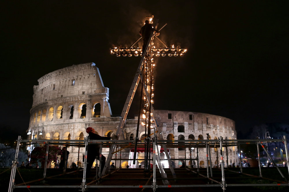 . A man climbs a cross lit with flames for the Way of The Cross procession at the Colosseum on Good Friday March 29, 2013 in Rome, Italy. Pope Francis is taking part in his first holy week as pontiff. The traditional Catholic procession of Via Crucis on Good Friday recalls the crucifixion of Jesus Christ with Holy Week ending with the celebration of Jesus Christ\'s resurrection on Easter Sunday.  (Photo by Franco Origlia/Getty Images)