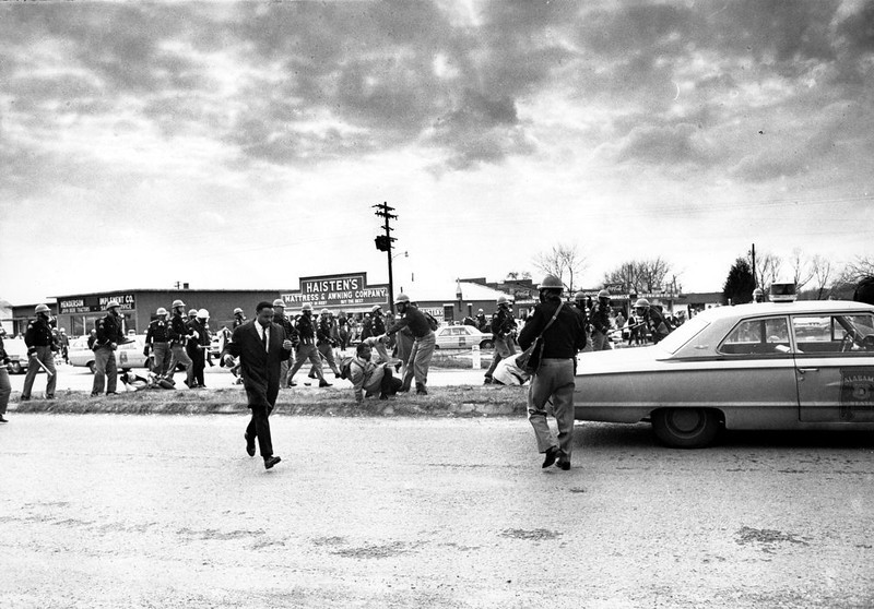 . March leader Hosea Williams, left, leaves the scene as state troopers break up the civil rights voter registration march in Selma, Ala., and put John Lewis, center, of the Student Non-violent Coordinating Committee on the ground on March 7, 1965.  (AP Photo/File)