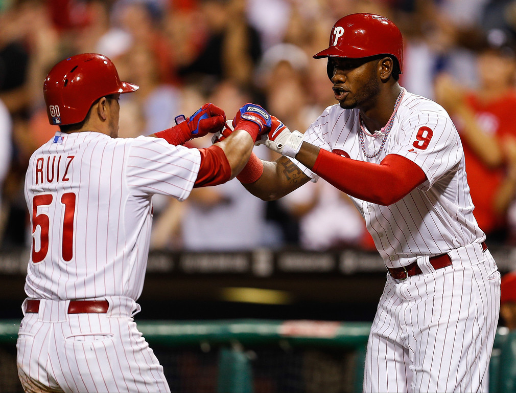 . Domonic Brown #9 of the Philadelphia Phillies congratulates Carlos Ruiz #51 after Ruiz hit a solo home run in the fifth inning of the game against the Colorado Rockies  at Citizens Bank Park on August 19, 2013 in Philadelphia, Pennsylvania. (Photo by Brian Garfinkel/Getty Images)