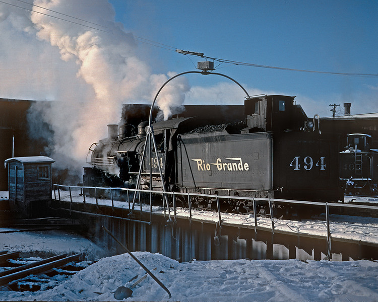 December 18, 1961.  It is a cold morning in Alamosa as 494 gets a spin on the turntable.  Shortly she will head out of town with the 487, flanger, spreader, and two cabooses to open up Cumbres for a freight that will be waiting for it at Antonito.  The freight will then follow ten minutes behind the snow clearing train.