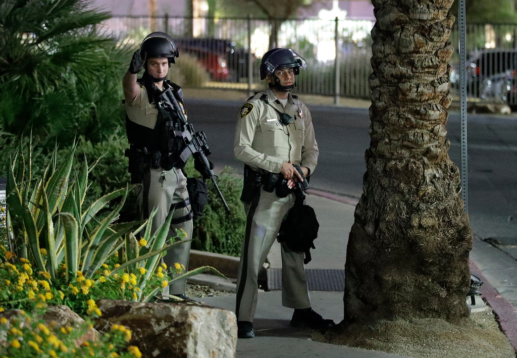 . Police officers take cover behind a tree at the Luxor resort and casino during a shooting on the Las Vegas Strip, Sunday, Oct. 1, 2017, in Las Vegas. (AP Photo/John Locher)