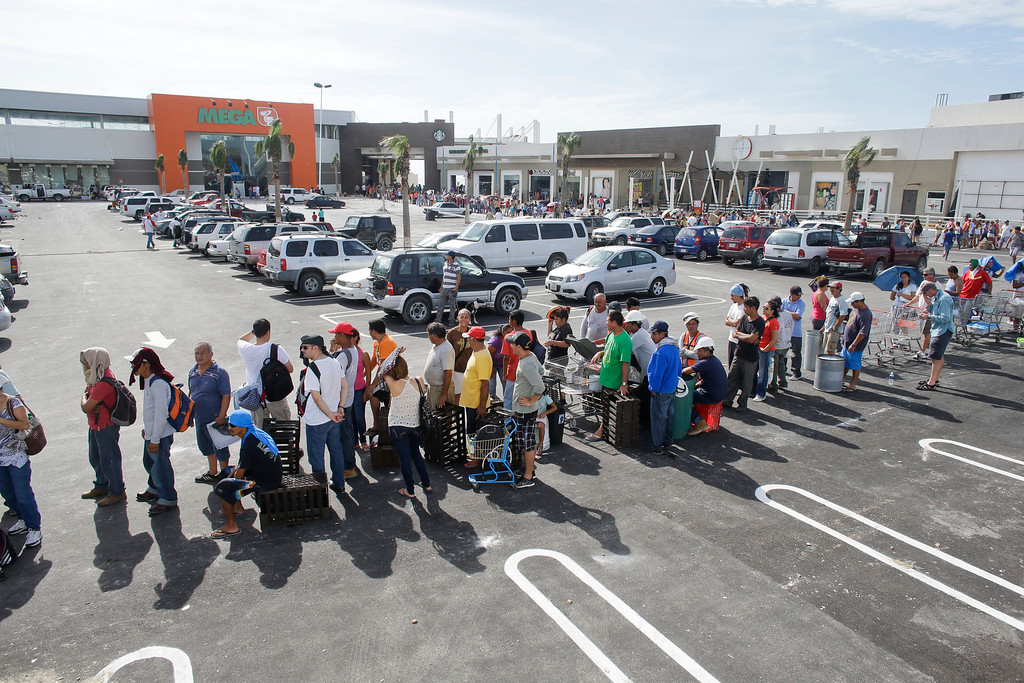 . People stand in line to get free food from a Mega supermarket in Los Cabos, Mexico,  Tuesday, Sept. 16, 2014. The employees said the company donated all the food at the market and established a system by which every person had 5 minutes to get whatever they could for free. (AP Photo/Victor R. Caivano)