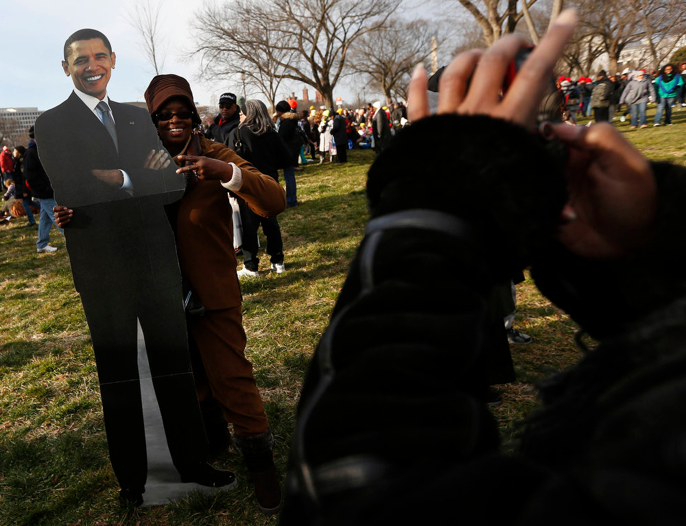 Description of . A woman poses for a picture with a card board cutout of U.S. President Barack Obama on the National Mall during the ceremonial swearing-in ceremonies on the West front of the U.S. Capitol in Washington January 21, 2013. REUTERS/Shannon Stapleton