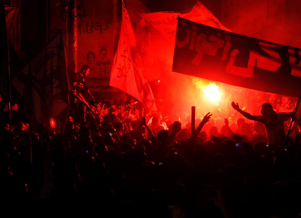 ". Members of Egypt s April 6 Youth Movement shout anti-Muslim Brotherhood slogans and light flares during a rally in front of general prosecutor office in Cairo, Egypt, Saturday, April 6, 2013. Thousands of activists took to the streets Saturday to mark the fifth anniversary of the founding of a leading opposition group, the April 6 Youth Movement, and to push a long list of demands on Morsi, including the formation of a more inclusive government amid a worsening economy. Arabic reads, ""private prosecutor for brotherhood.\"" (AP Photo/ Amr Nabil)"