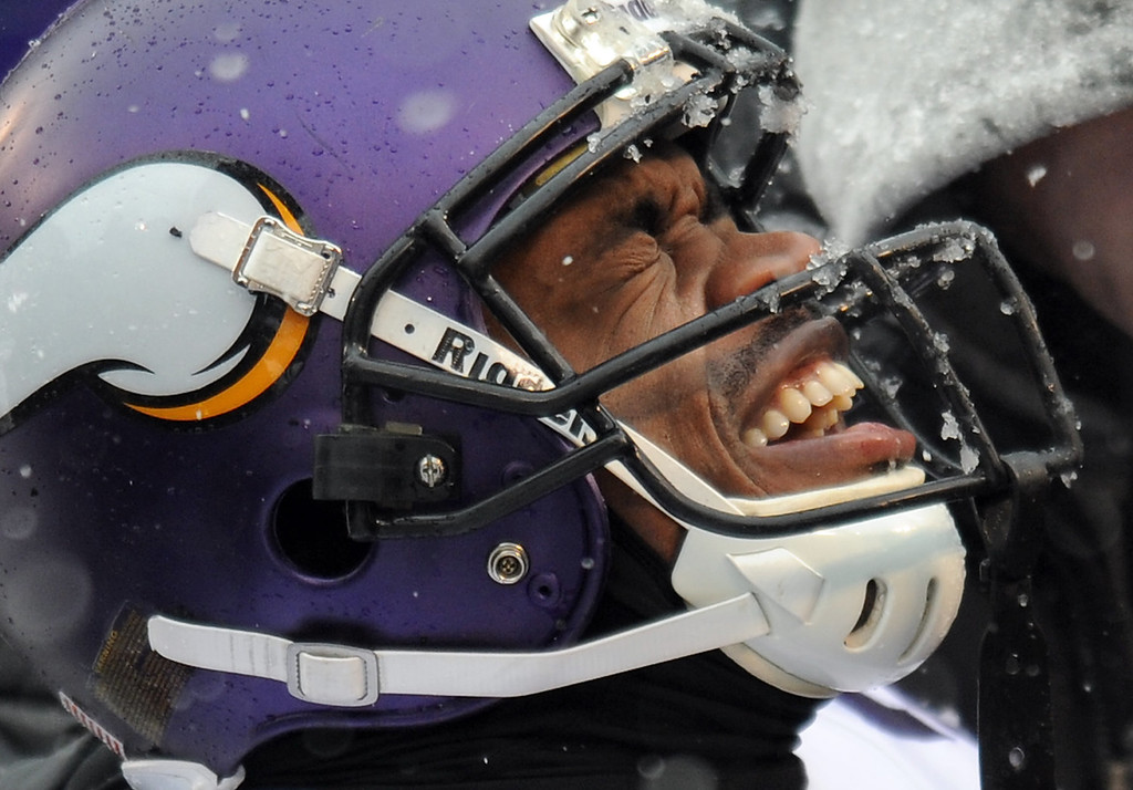 . Minnesota Vikings running back Adrian Peterson reacts as he is tended to after injuring his ankle on a play in the second quarter of an NFL football game against the Baltimore Ravens, Sunday, Dec. 8, 2013, in Baltimore. (AP Photo/Gail Burton)
