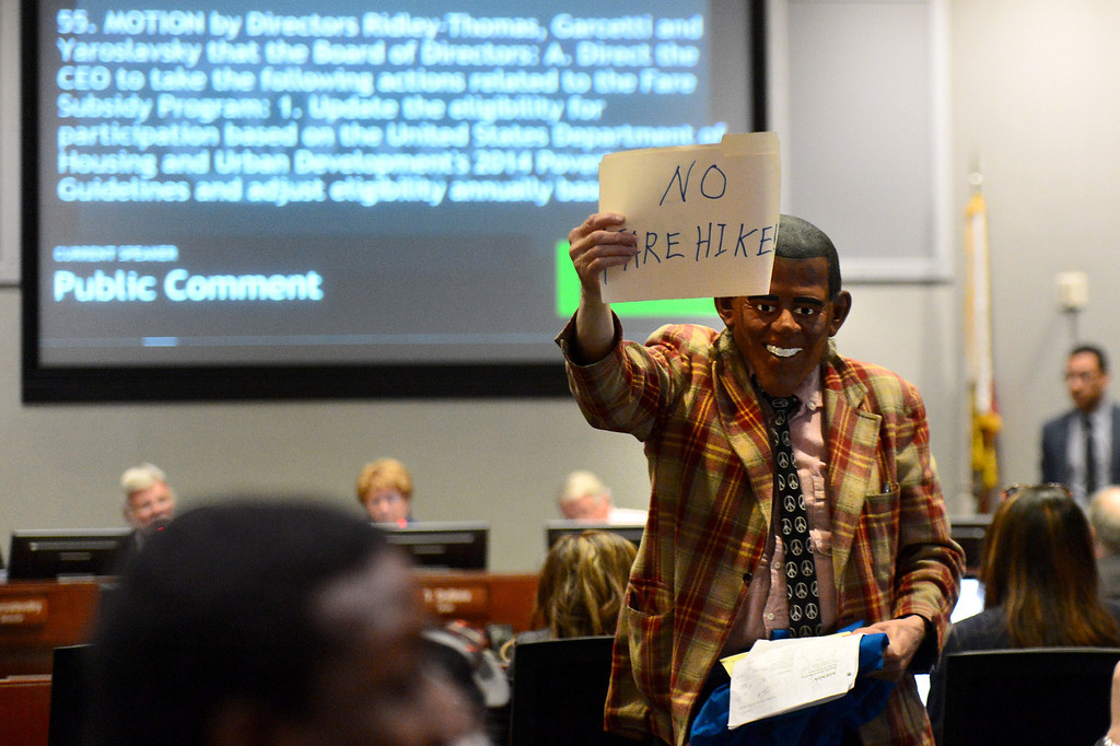 . During public comment gadfly John Walsh, wearing a President Obama mask, protests the MTA board meeting\'s vote for a major fare increase Thursday, May 22, 2014. The increase will effect 500,000 riders of trains, subways and buses in Los Angeles County. Students rates will not increase. (Photo by Sarah Reingewirtz/Pasadena Star-News)