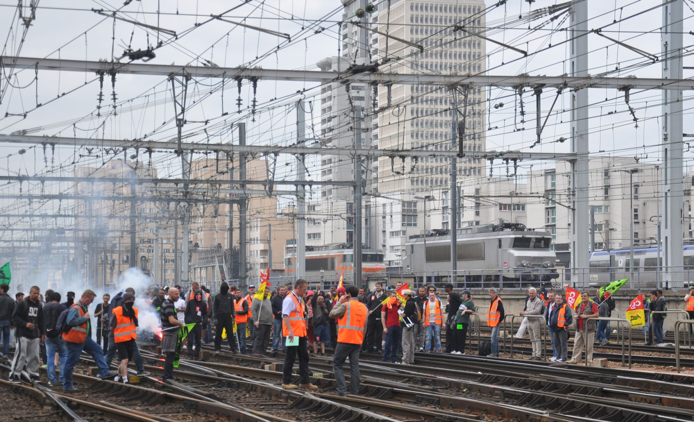 Description of . Striking workers of the French state-run rail operator SNCF, backed by French unions CGT and Sud-Rail, stage a demonstration on the rail-tracks at the Montparnasse train station in Paris, against reform plans proposed by the French government on June 17, 2014. France's longest rail strike in years rolled on for a second week as lawmakers were set to debate a contentious debt-cutting reform plan opposed by unions. (WILLIAM DELAPORTE/AFP/Getty Images)