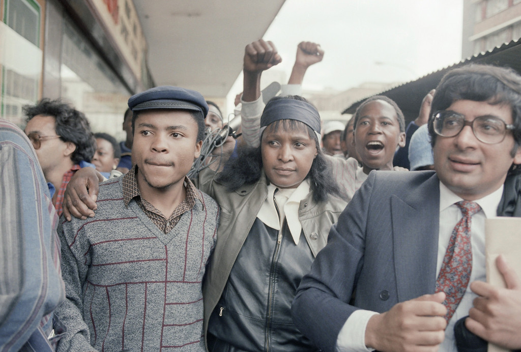 . Black activist, Mrs. Winnie Mandela, raises a clenched fist after appearing briefly in the Johannesburg Magistrate\'s Court, Monday, Jan. 22, 1986. Mrs. Mandela, who was held by police in Soweto on Sunday for defying her banning order, was released on her own recognizance\'s and ordered to appear in the Krugersdorp Magistrate\'s Court, west of Johannesburg. (AP Photo/Greg English)