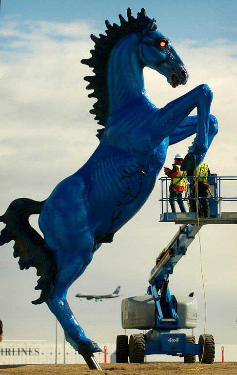 """. With a plane landing in the background, workmen John Van Aucken (right) and Serge Labesque (left, red jacket) work on an access plate on the chest of the 32 foot tall fiberglass \""""Mustang\"""" by artist Luis Jimenez that is being installed outside of Denver International Airport  on Tuesday, February 12, 2008.   Cyrus McCrimmon, The Denver Post"""