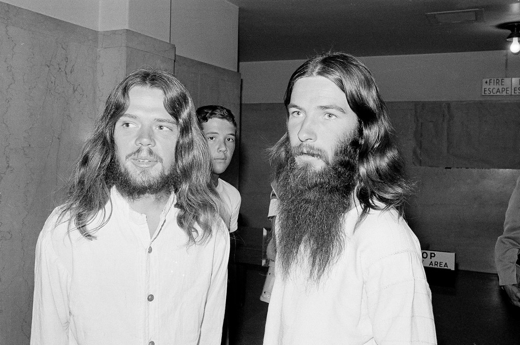 . Bob Kasabian, left, waits outside a Los Angeles courtroom, July 27, 1970, where his wife Linda is due to take the stand to describe what she saw the night that actress Sharon Tate and four others were murdered. She is expected to be the state\'s principal witness in the trial of Charles Manson and three female companions. Man at right is Kasabian\'s friend, Charles Melton. (AP Photo/Wally Fong)