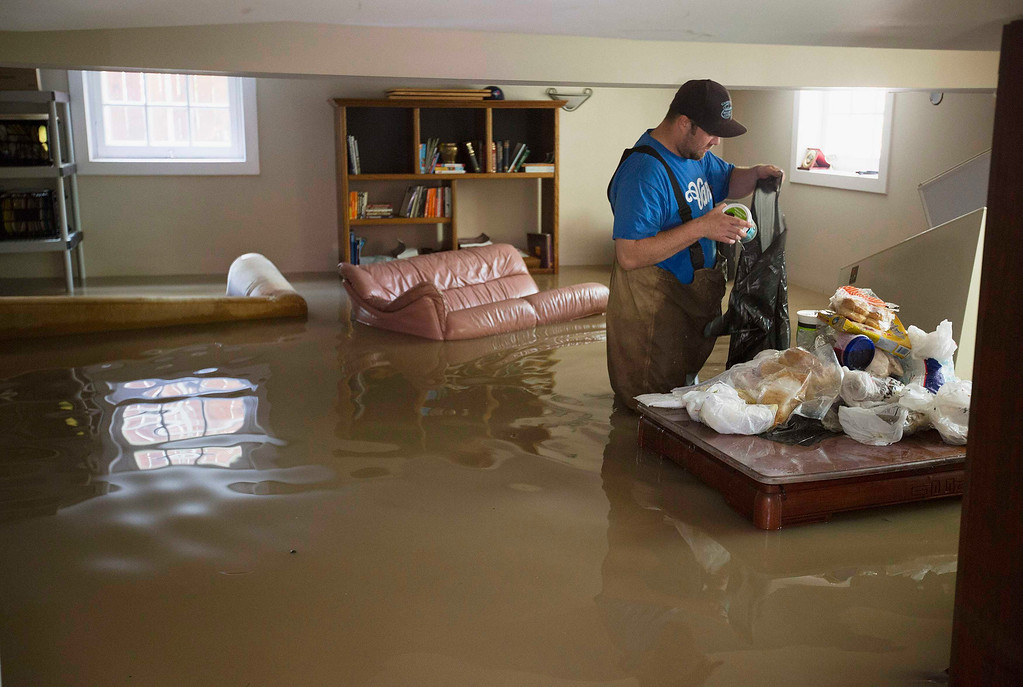 . Cody Scott throws food away from a freezer trapped in a flooded basement in the Elbow Park area of Calgary, Alberta June 22, 2013.   REUTERS/Todd Korol