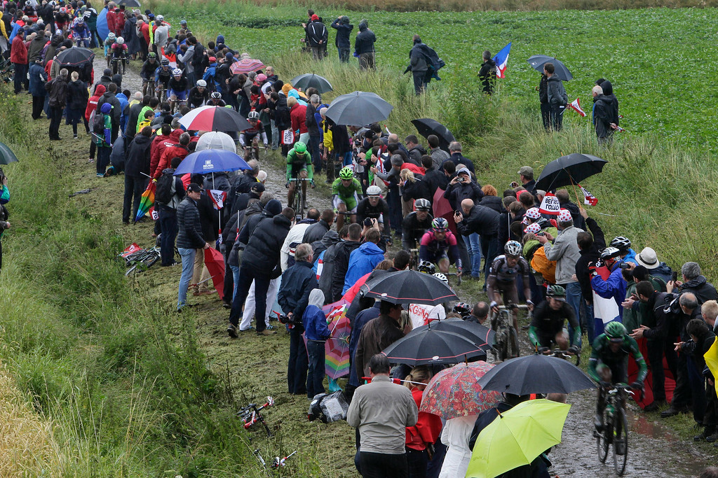 . The pack rides on a cobblestone-paved section of road  in Ennevelin, northern France, Wednesday July 9, 2014, during the fifth stage of the Tour de France cycling race over 155 kilometers (96,7 miles) with the start in Ypres, Belgium and finish in Arenberg, France. (AP Photo/Michel Spingler)
