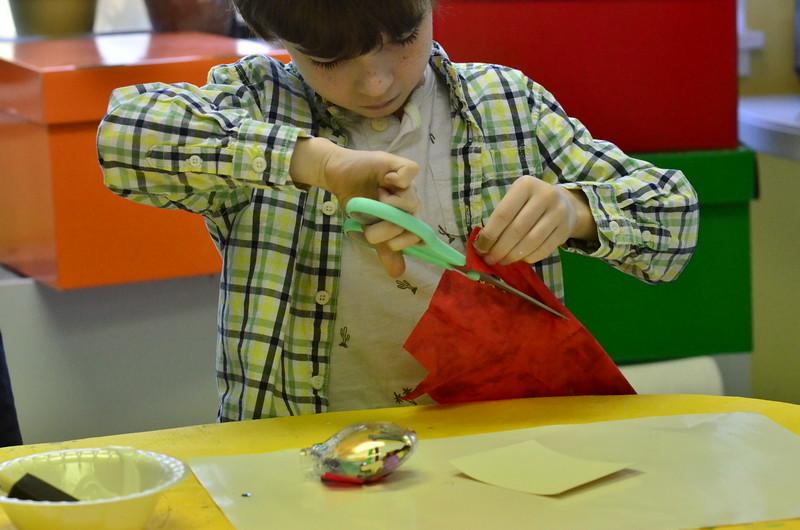 Ian cutting fabric in art class.