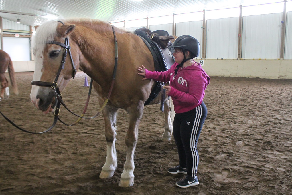 . Kathy Habat pets  the horse she rode during an equine therapy exercise at Fieldstone Farm . Kristi Garabrandt - The News-Herald