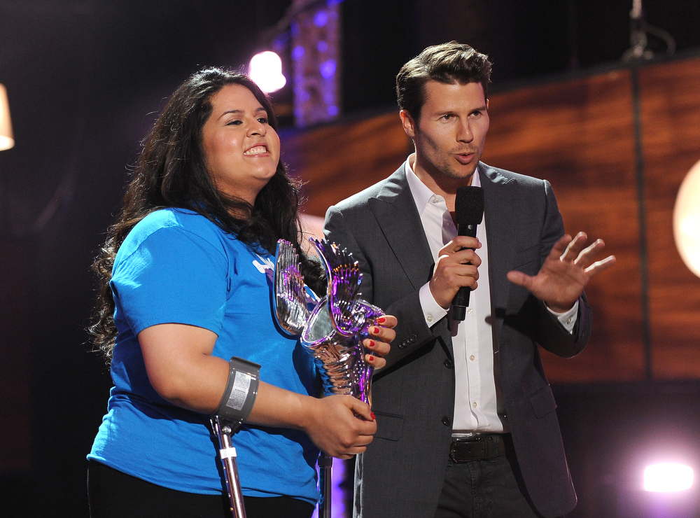. Award recipient Lorella Praeli of United We Dream and host Jason Dundas speak onstage at the DoSomething.org and VH1\'s 2013 Do Something Awards at Avalon on July 31, 2013 in Hollywood, California.  (Photo by Kevin Winter/Getty Images)