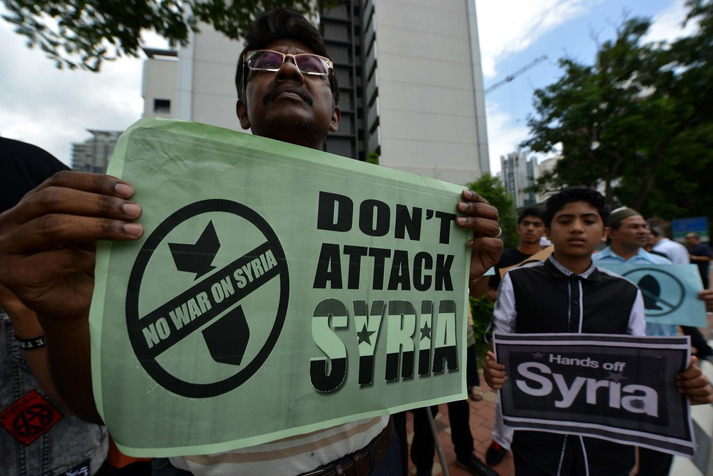 . Demonstrators hold placards during a rally against a US intervention in Syria outside the US embassy after Friday prayer in Kuala Lumpur on September 6, 2013.  World powers discussed the Syria crisis over dinner at the G20 summit in Russia on September 5, but failed to bridge deeply entrenched divisions over a US push for military action against President Bashar al-Assad\'s regime. MOHD RASFAN/AFP/Getty Images