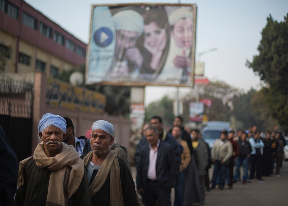 . Egyptians line up to vote in the country\'s constitutional referendum in Cairo, Egypt, Wednesday, Jan. 15, 2014. Undeterred by a day of sporadic violence, Egyptians are lining up to vote on the second, final day of a key referendum on a new constitution. (AP Photo/Khalil Hamra)