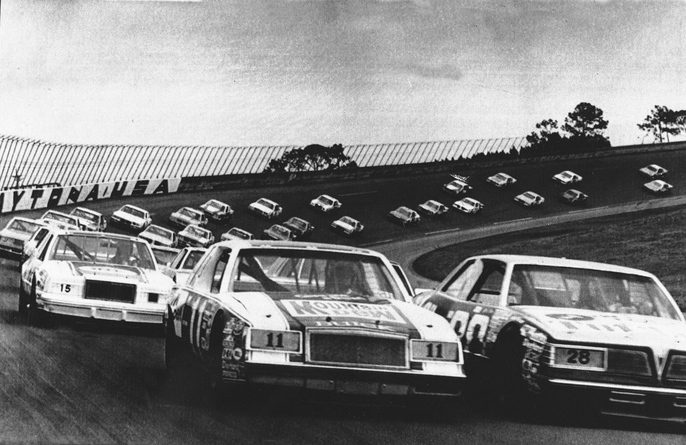 Description of . Forty-two Grand National cars take off for the start of the Daytona 500 at the Daytona International Speedway, Daytona Beach, Fla., Feb. 15, 1981, with Bobby Allison (28) and Darrell Waltrip (11) leading the pace.  (AP Photo/Phil Sandlin)