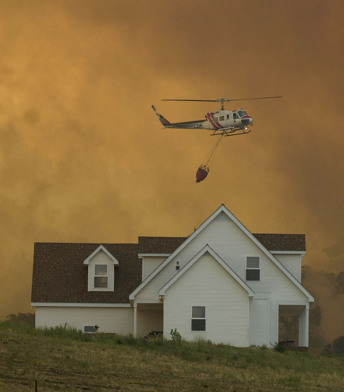 . A helicoptor rises behind a house as crews prepare to drop water on a smoldering hillside outside of Julian, Calif. Oct. 29, 2003. Firefighers were trying to keep the 250,000 acre Cedar fire from spreading into the mountain towns east of San Diego. (AP Photo/Charlie Riedel)