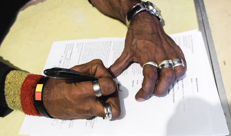 Aboriginal Man signing a Form
