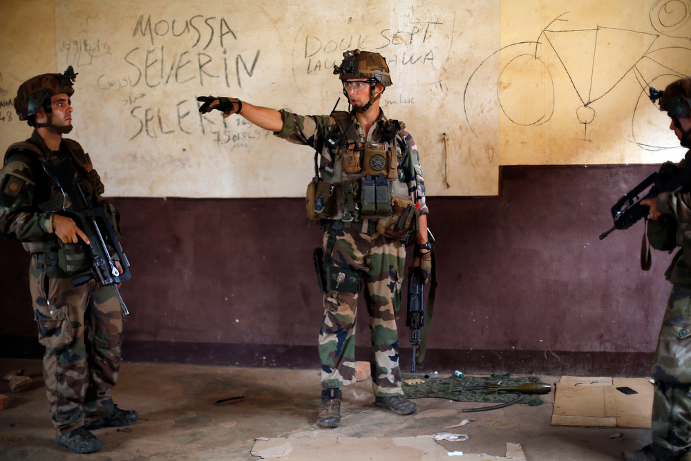 . French troops search and secure inspect barracks left by Seleka Muslim militias after they evacuated the Kasai camp in Bangui, Central African Republic, Tuesday Jan. 28, 2014, to relocate and join other Selekas at the PK11camp. The departure of the fighters was greeted with screams of joy from the crowd of hundreds that gathered to watch them leave for another camp in northern Bangui. �We are free! This is our new year!� they shouted. Seleka became deeply unpopular after they killed and tortured civilians after seizing power in March 2013. Their leader Michel Djotodia stepped down as president earlier this month and went into exile in Benin. (AP Photo/Jerome Delay)