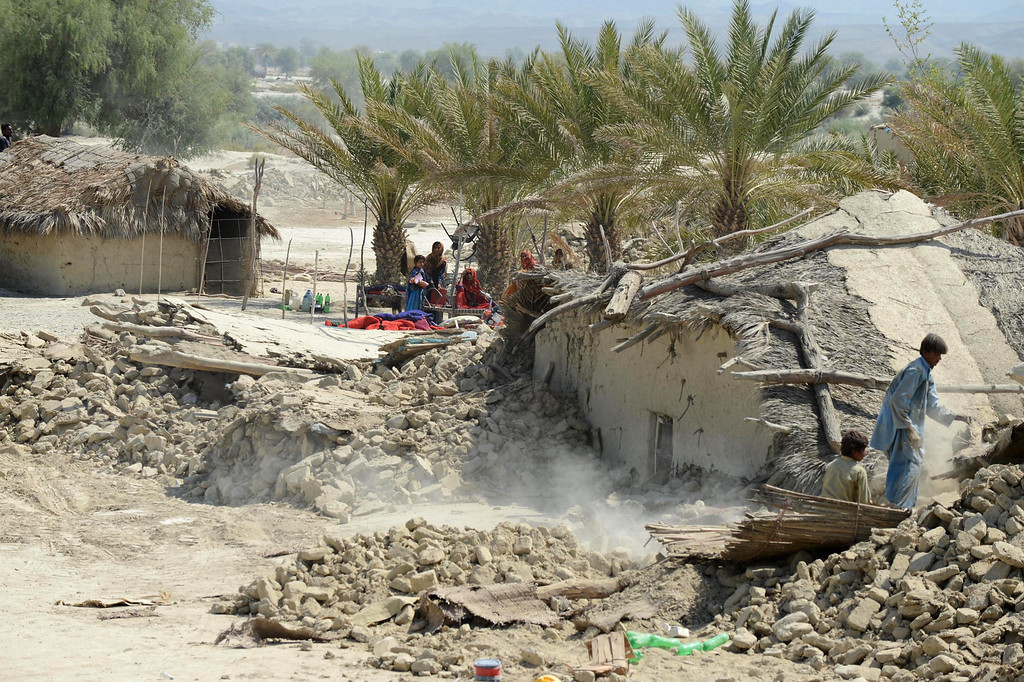 . Pakistani earthquake survivors search through the debris of their collapsed houses in the devastated district of Awaran on September 25, 2013.  AFP PHOTO/Banaran KHAN/AFP/Getty Images
