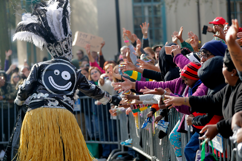 . A member of the Krewe of Zulu hands out coconuts to the crowd as their parade rolls on Mardi Gras day in New Orleans, Tuesday, Feb. 13, 2018. (AP Photo/Gerald Herbert)
