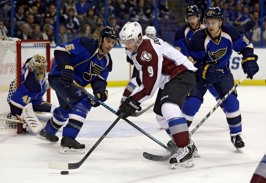. Colorado Avalanche\'s Matt Duchene (9) tries to control the puck as St. Louis Blues goalie Jaroslav Halak, of Slovakia, Barret Jackman (5) and Kevin Shattenkirk, right, defend during the first period of an NHL hockey game Thursday, Nov. 14, 2013, in St. Louis. (AP Photo/Jeff Roberson)