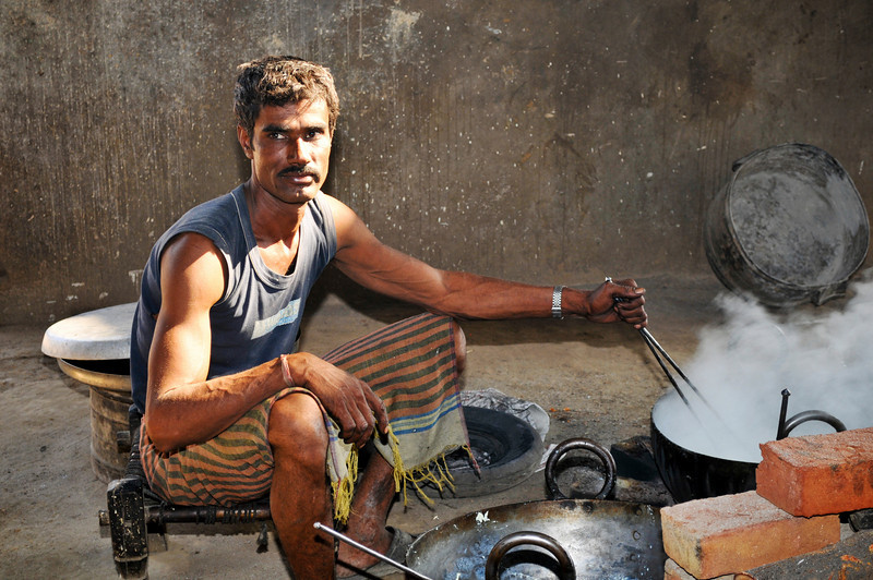 Man boiling milk to condensate in a shop in Rajasthan. About 12 men were working in the hot place.