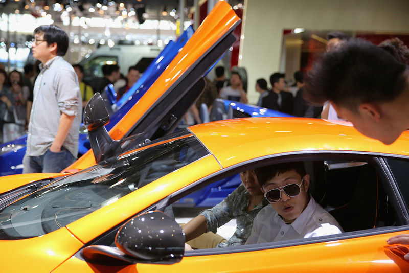 . The potential consumers sit in a McLaren sport car during the 2014 Beijing International Automotive Exhibition at China International Exhibition Center on April 22, 2014 in Beijing, China. More than 2,000 automotive enterprises from 14 countries and regions participated in the 2014 Beijing International Automotive Exhibition from April 20 to April 29.  (Photo by Feng Li/Getty Images)